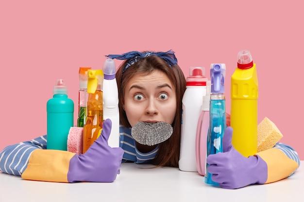 Przerażona młoda kobieta ma wyskakujące oczy, trzyma gąbkę w ustach, obejmuje środki czystości, oszołomiona dużą ilością pracy nad domem