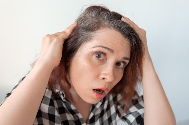 Przerażona młoda kobieta patrząca w lustro, wpatrująca się z otwartymi ustami w pierwsze siwe włosy na jej głowie, a
