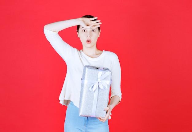 Przerażona młoda kobieta trzyma pudełko i stoi na czerwonej ścianie