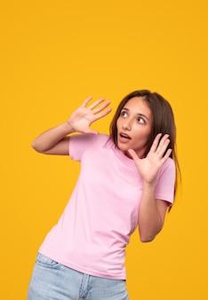 Przerażona młoda kobieta w zwykłym ubraniu gestykulująca i odwracająca wzrok, próbująca uniknąć niebezpieczeństwa na żółtym tle