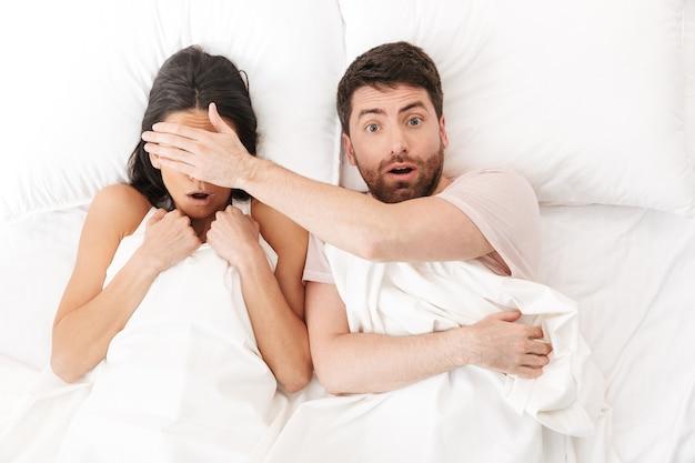 Przerażona młoda, kochająca się para leży w łóżku chowając się pod kocem zakrywającym oczy