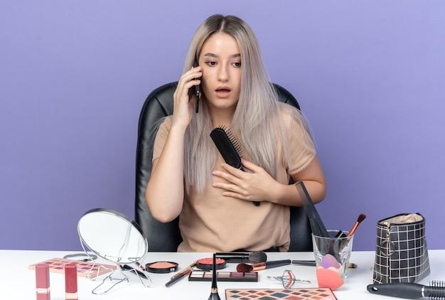Przerażona młoda piękna dziewczyna siedzi przy stole z narzędziami do makijażu, mówi na telefonie trzymając grzebień na białym tle na niebieskim tle
