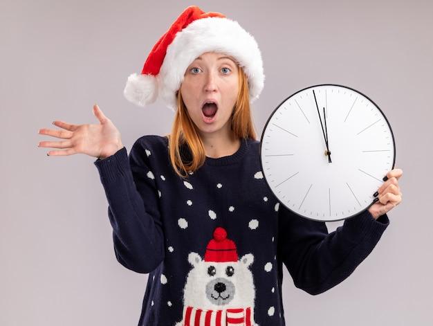 Przerażona młoda piękna dziewczyna w świątecznym kapeluszu trzymająca zegar ścienny rozkładający rękę na białej ścianie