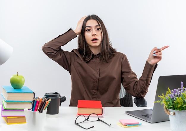 Przerażona młoda szkolna kobieta siedzi przy stole z szkolnymi narzędziami wskazującymi z boku, kładąc dłoń na głowie