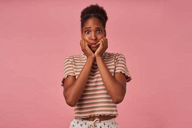 Przerażona młoda, urocza, kręcona brunetka trzymająca się za ręce na policzkach, patrząc przestraszona z przodu, stojąca nad różową ścianą