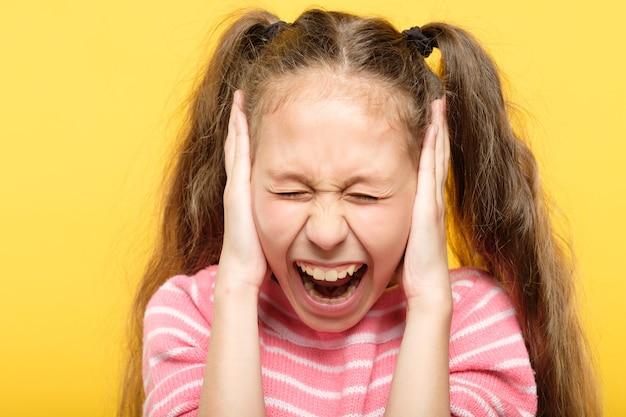 Przerażona, skamieniała krzycząca dziewczyna zakrywająca uszy. stres i załamanie emocjonalne.
