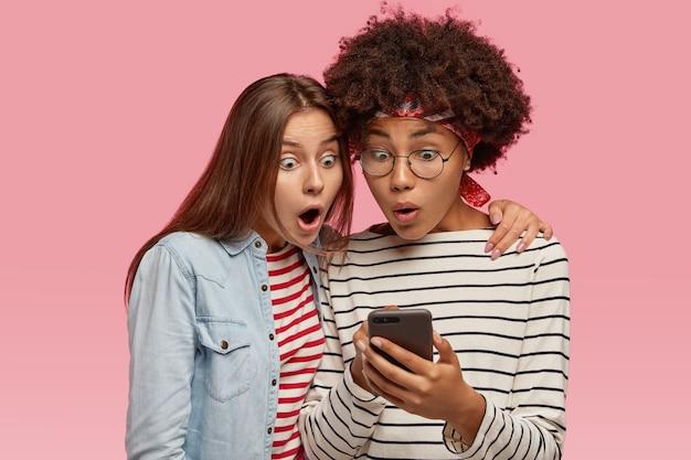Przerażone wieloetniczne kobiety wpatrują się z podsłuchami w ekran telefonu komórkowego, czytają wspaniałe wiadomości, wzdychają ze zdumienia