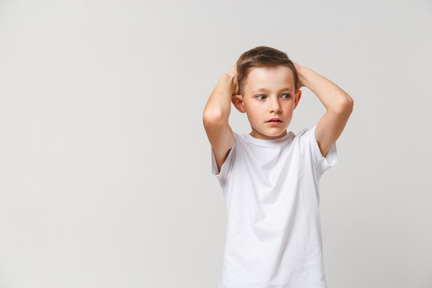 Przerażony chłopiec w białej koszulce z obiema rękami na głowie na szarym tle