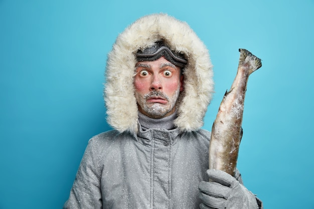 Przerażony emocjonalny mężczyzna z czerwoną twarzą pokrytą szronem wyrusza na ryby podczas zimowej wyprawy trzyma dużą rybę w kurtce i goglach narciarskich.