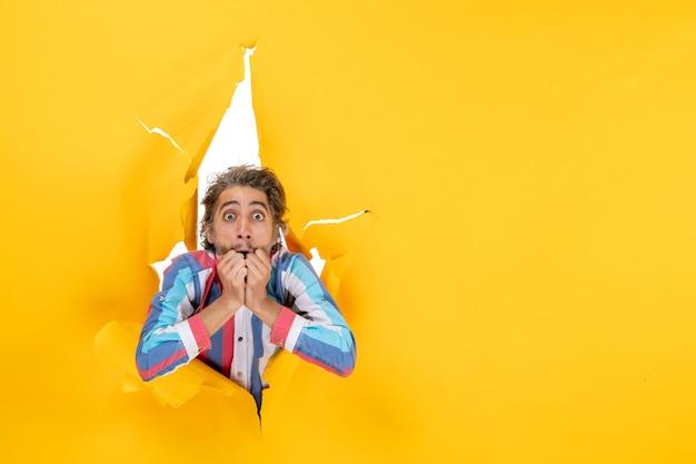 Przerażony i emocjonalny młody facet pozuje do kamery przez rozdartą dziurę w żółtym papierze
