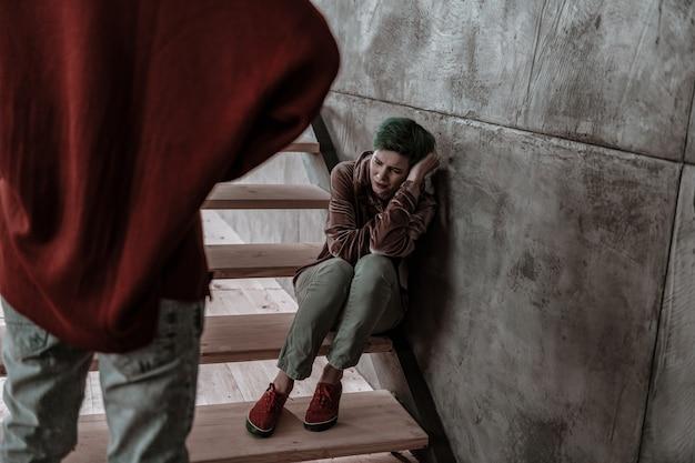 Przerażony i przestraszony. młoda zielonowłosa dziewczyna czuje się przerażona i boi się rozzłoszczonego chłopaka