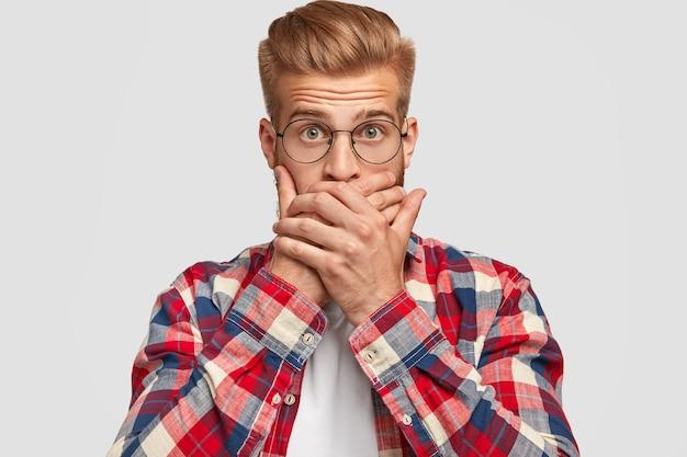 Przerażony kaukaski mężczyzna z przestraszonym wyrazem twarzy, zakrywający usta, starając się zachować informacje w tajemnicy, zdziwiony, odizolowany na białej ścianie. przystojny hipster ma modną fryzurę i rude włosie