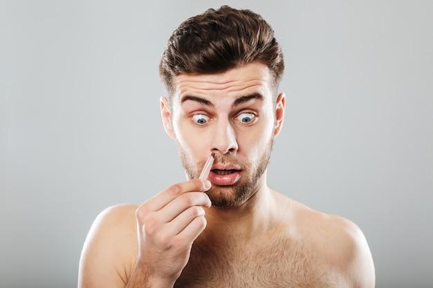 Przerażony mężczyzna usuwa włosy z nosa pęsetą