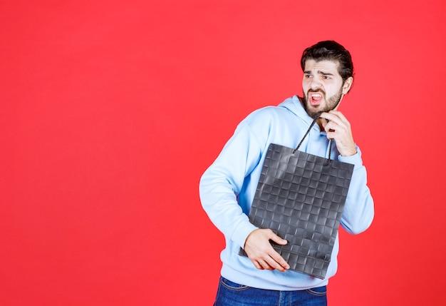 Przerażony młody człowiek trzymający torbę i biegający