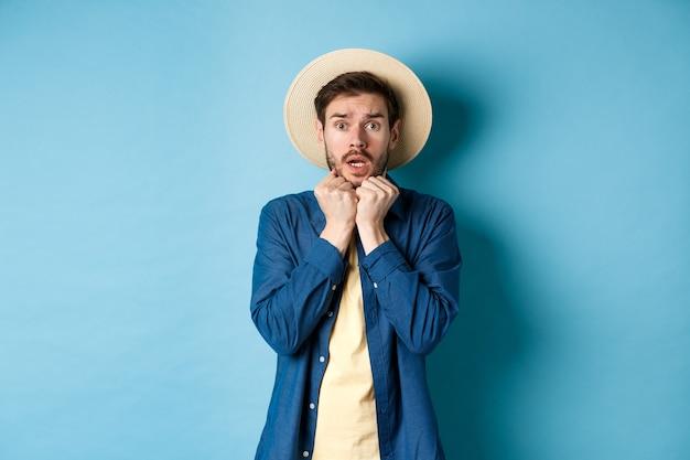 Przerażony młody turysta, drżący ze strachu, patrząc na coś strasznego na wakacjach, w słomkowym kapeluszu, stojący na niebieskim tle.