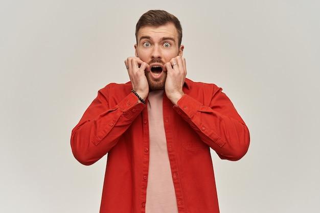 Przerażony, przerażony młody brodaty mężczyzna w czerwonej koszuli wygląda na przestraszonego i krzyczy nad białą ścianą