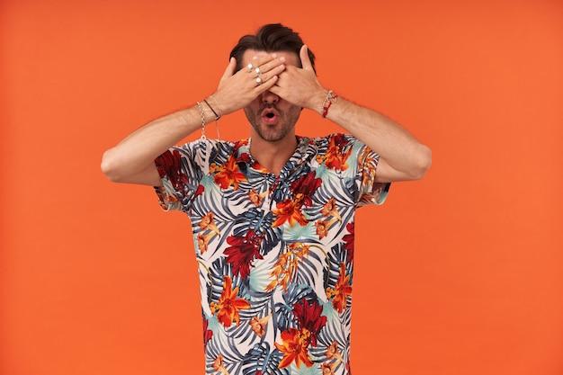 Przerażony, przestraszony młody mężczyzna z włosiem w hawajskiej koszuli c