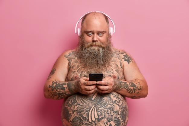 Przerażony, zarozumiały mężczyzna z gęstą brodą wpatruje się w wyświetlacz smartfona, czyta szokujące wiadomości, przewija portale społecznościowe, pozuje nago, ma gruby brzuszek od piwa, lubi słuchać muzyki, dobry, doskonały dźwięk