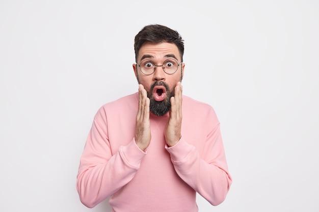 Przerażony zaskoczony brodaty mężczyzna trzyma ręce na twarzy, wygląda na onieśmielony