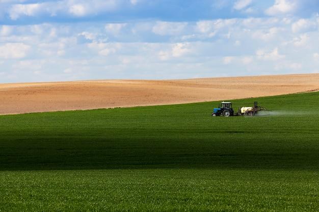 Przeróbka zboża - traktor fotografowany na polu rolnym podczas obchodzenia się z pestycydami. niebo z chmurami