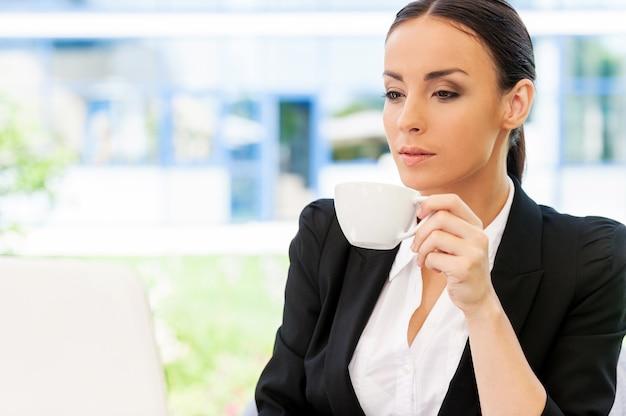 Przerwa na kawę. atrakcyjna młoda kobieta w stroju formalnym pracuje na laptopie i uśmiecha się siedząc w kawiarni na chodniku