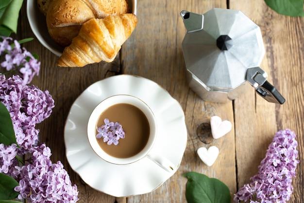 Przerwa na kawę. bukiet bzu z filiżanką latte. liliowy w dziewczynie na pulpicie.