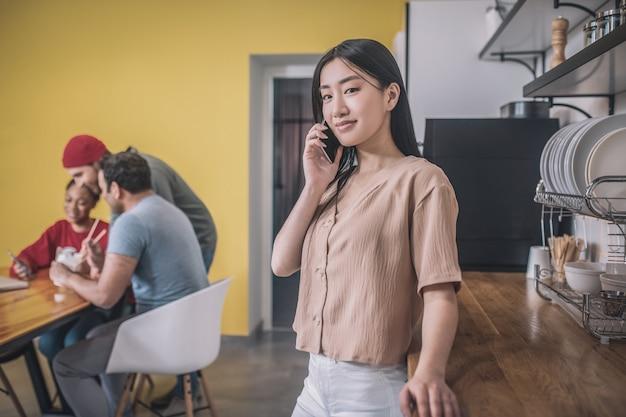 Przerwa na kawę. cute asian girl kawie z kolegami i rozmawia przez telefon