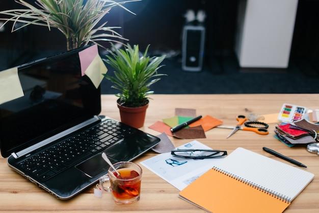 Przerwa na kawę. czas na ponowne uruchomienie i relaks. filiżanka herbaty stojąca na biurku w wygodnym, nowoczesnym biurze z rozrzuconymi artykułami papierniczymi i materiałami eksploatacyjnymi