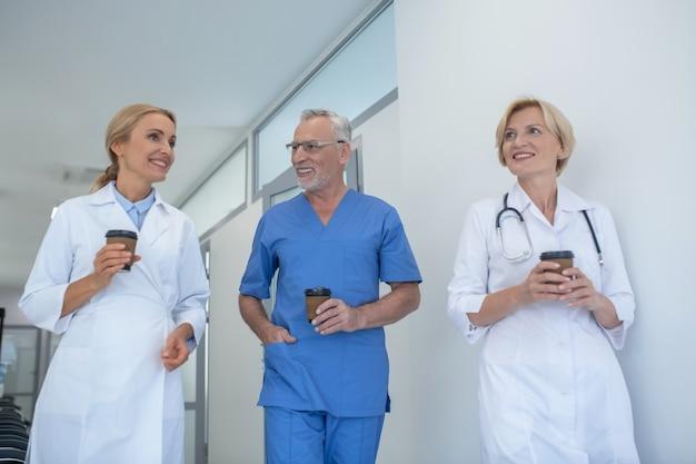 Przerwa na kawę. grupa uśmiechniętych lekarzy pijących kawę na korytarzu, po przyjacielskiej rozmowie