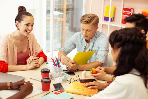 Przerwa na kawę. ładna brunetka z uśmiechem na twarzy podczas rozmowy z kolegami z grupy