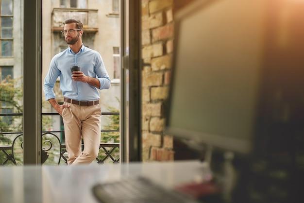 Przerwa na kawę młody i przystojny brodaty mężczyzna w okularach i stroju wizytowym, trzymając kubek