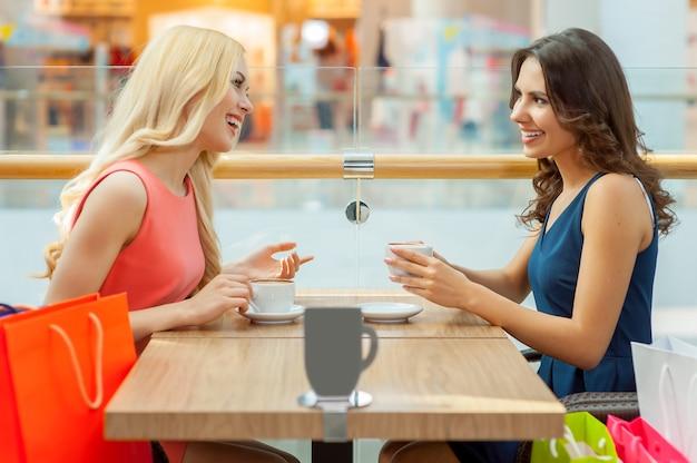 Przerwa na kawę po zakupach. dwie piękne młode kobiety pijące kawę w restauracji?