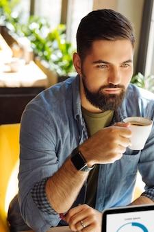 Przerwa na kawę. poważny brodaty mężczyzna siedzący z filiżanką kawy podczas przerwy na kawę