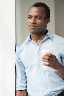Przerwa na kawę. przystojny młody czarny mężczyzna w niebieskiej koszuli trzymający filiżankę kawy i patrzący przez okno