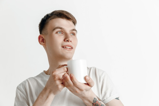 Przerwa na kawę. przystojny młody mężczyzna trzyma filiżankę kawy, uśmiechając się stojąc przed szarym tle studio