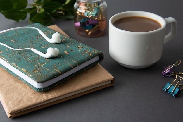 Przerwa na kawę. stół roboczy z notatnikami, artykułami biurowymi i filiżanką kawy.