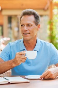 Przerwa na kawę. wesoły dojrzały mężczyzna pijący kawę siedzący przy stole na zewnątrz z domem w tle