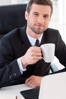 Przerwa na kawę. widok z góry pewny siebie młody człowiek w formalwear pije kawę i uśmiecha się siedząc w swoim miejscu pracy