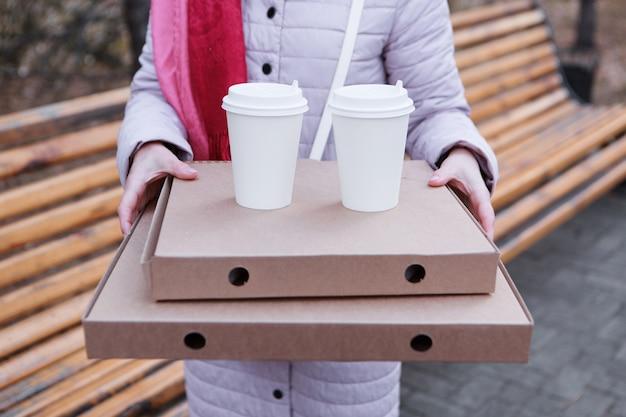 Przerwa na lunch dziewczyna zjada ciasto i pije kawę w parku na ławce dostarczanie jedzenia chęć sp...