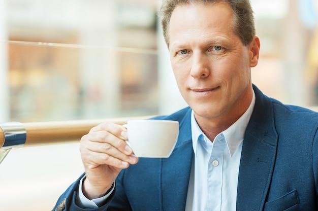 Przerwa przy świeżej kawie. wesoły dojrzały mężczyzna w stroju formalnym pijący kawę i uśmiechający się siedząc w kawiarni