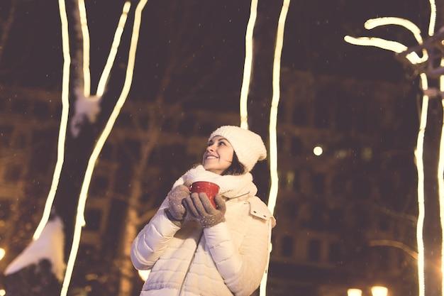 Przerwa świąteczna. piękna uśmiechnięta kobieta w ciepłej odzieży z filiżanką gorącej kawy na świeżym powietrzu w zimie. noc miasta.