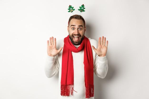 Przerwa świąteczna. podekscytowany brodaty mężczyzna podnoszący ręce do góry i krzyczący z radości, świętujący przyjęcie sylwestrowe, stojący na białym tle