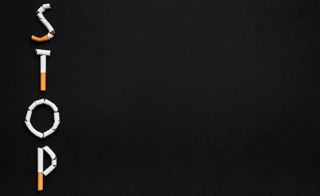Przerwa tekst układający z papierosem przeciw czarnemu tłu