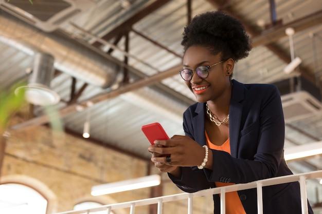 Przerwa w pracy. stylowa ciemnoskóra kobieta pisze sms-a do koleżanki podczas przerwy w pracy