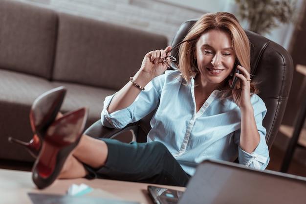 Przerwa w pracy. stylowa dojrzała prawniczka w szpilkach, ciesząca się przerwą w pracy podczas rozmowy przez telefon