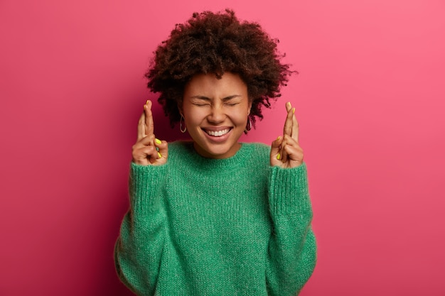 Przesądna afroamerykanka nastawiona na zwycięstwo, liczy na pozytywny wynik, trzyma kciuki i radośnie uśmiecha się, nosi zielony sweter, oczekuje ważnych wiadomości, odizolowana na różowej ścianie