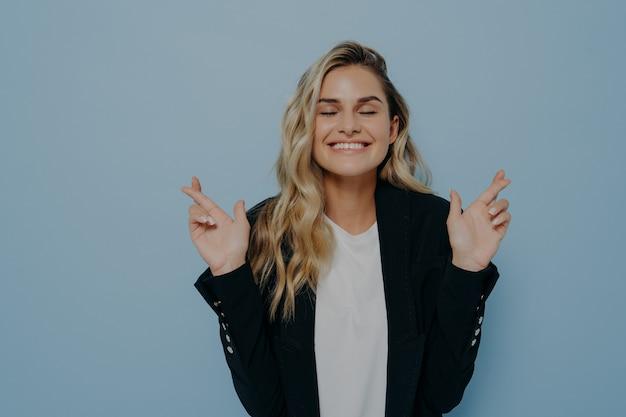 Przesądna młoda studentka o blond włosach krzyżujących palce obiema rękami, przywołująca szczęście przed ważnym egzaminem lub wydarzeniem, ma nadzieję na zwycięstwo i sukces, z nadzieją zamyka oczy