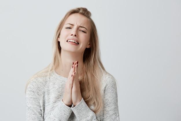Przesądny religijny modli się piękna kobieta z blond prostymi włosami, płacząca, zaciskająca dłonie na szczęście, mając nadzieję, że spełnią się życzenia, mając podekscytowany wygląd. ludzkie emocje, uczucia