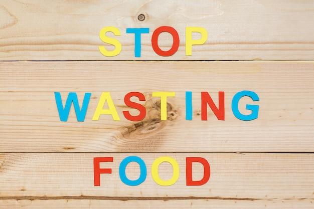 Przestań marnować jedzenie. napis liter wycięty z kolorowej tektury na drewnianym tle. koncepcja marnotrawienia żywności