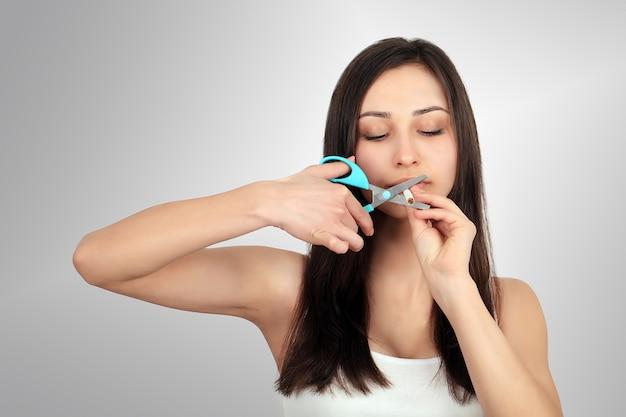 Przestań palić . młoda kobieta cięcia papierosów nożyczkami szczęśliwy uśmiechnięty. skoncentruj się na dłoni, nożyczkach i papierosach